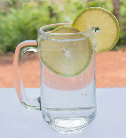 sparkling water: lemon soda, sparkling water, white table. Stock Photo