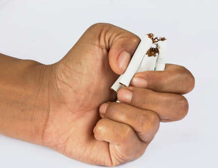 breaking: Human hands breaking a cigarettes. Stock Photo