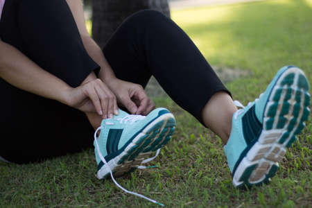 Young woman trying to lace up her sneakers Stock Photo