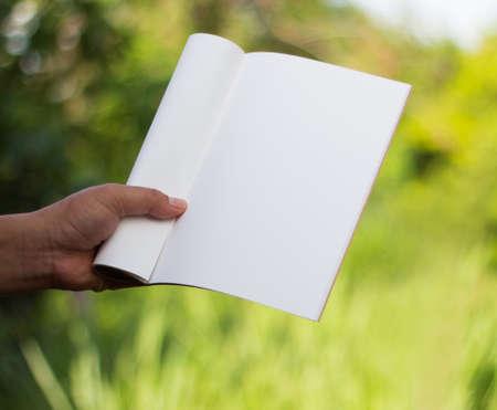 Hand holding white journal. Stock Photo
