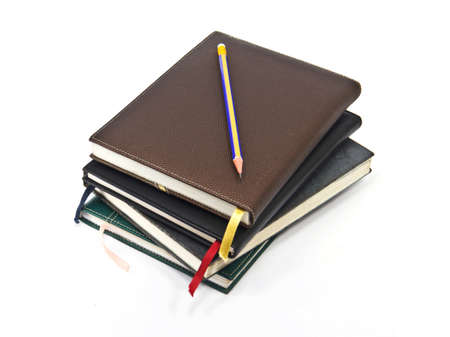 Pencil and old diary on white background photo