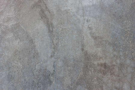 Textuur van de grijze gepolijst betonnen muur met krassen
