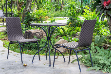 patio furniture: table and chairs standing on patio furniture in a beautiful garden. Stock Photo