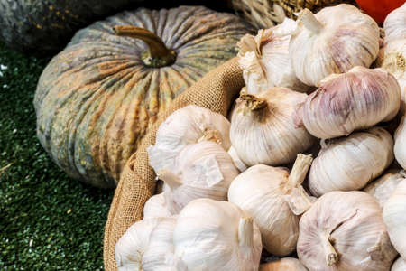Garlic in sack bag on green artificial grass background photo