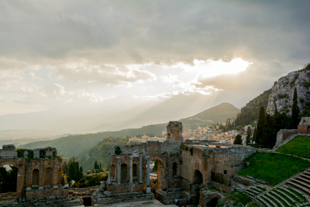 sun lit: Ruins of the ancient greek theater of Taormina, Sicily the Etna with its double snook tail in the background above the morning sun lit Giardini-Naxos bay