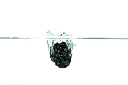 Black Blackberry falling into water with a splash