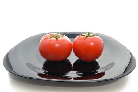 advertize: Two fresh tomatoes with green stems on a black plate isolated on white background Stock Photo