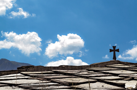 sanctified: A christian cross on the roof of a small church