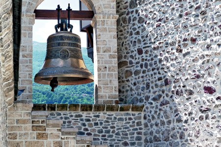 Church bell and rustic stone wall
