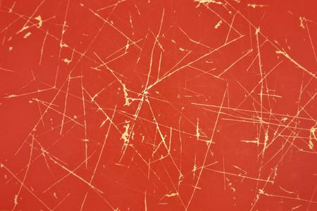プラスチック製の赤の背景に明るい傷