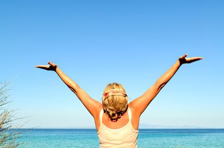 Cheerful woman with arms raised to the sky near the sea photo
