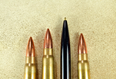 Pen and bullets as conceptual expression of the power of words photo