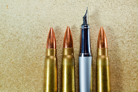 Pen and three bullets arranged verticaly on vintage background photo