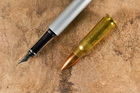 Fountain pen and a bullet in a parallel position on vintage background photo