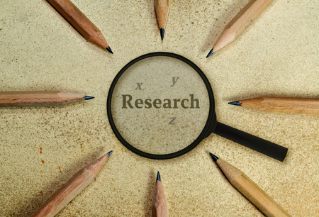 Word Research under a magnifying glass on vintage background photo