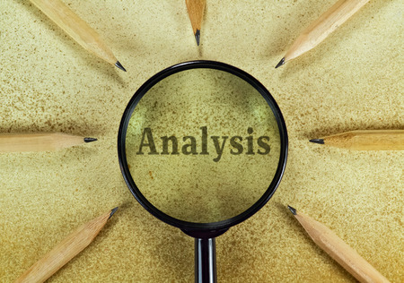 Word Analysis under magnifying glass on vintage background photo