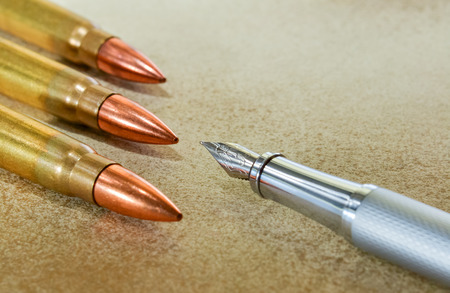 Silver fountain pen and three bullets arranged in the corners of the image photo