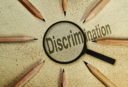 discriminacion: Palabra discriminaci�n bajo una lupa como una imagen conceptual acerca de los fen�menos