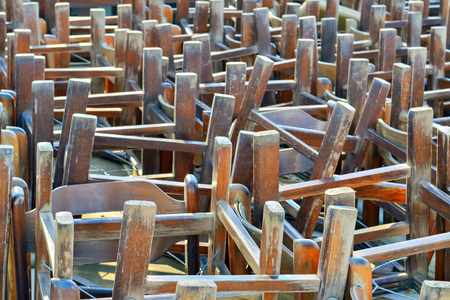 Pile of old restaurant chairs turned upside down after working hours photo