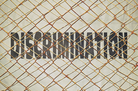 disallow: Conceptual image with the word Discrimination under a wire netting Stock Photo