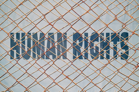 repress: Concept about the guaranteed human rights with text written under a wire fence Stock Photo