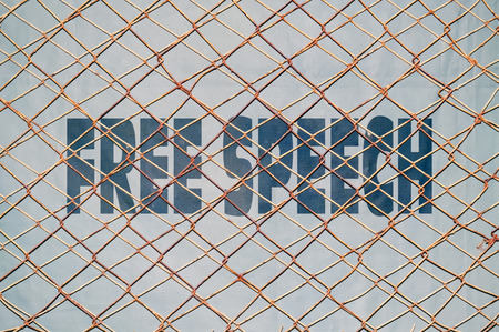 free speech: Concept about the rights to free speech with text written under a wire fence Stock Photo