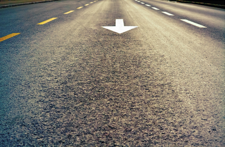 low angles: Closeup of highway and white arrow photographed from the lower angle Stock Photo
