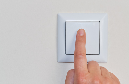 A hand of a woman pressing a wall mounted light switch