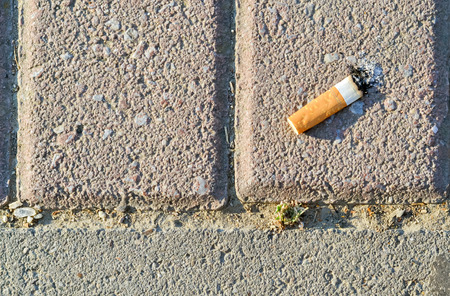 the thrown: Closeup of a cigarette butt thrown on the pavement Stock Photo