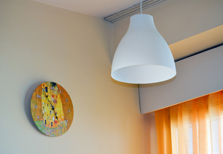 plafond: Wall clock and chandelier near the window in the living room