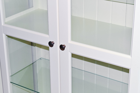 Closeup of an empty white cabinet with glass door Stock Photo
