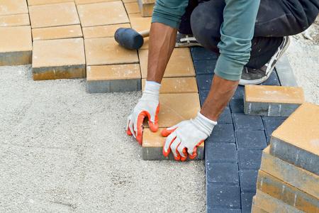 歩道を舗装中の労働者の手のクローズ アップ
