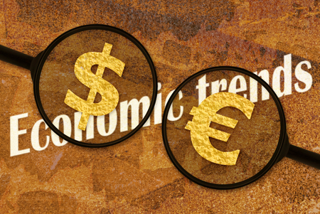 monetary devaluation: Text Economic Trends under magnifiers placed on dark background Stock Photo
