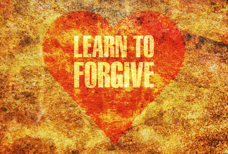 Text Learn to Forgive written with golden letters on a red heart