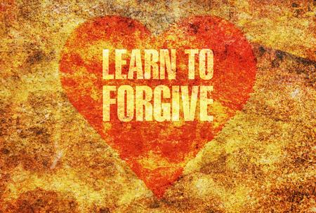 pardon: Texte apprendre à pardonner écrite en lettres d'or sur un coeur rouge Banque d'images