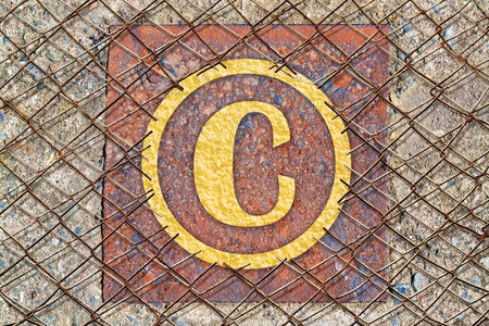 authorship: Copyright symbol written in golden color under a broken wire fence Stock Photo