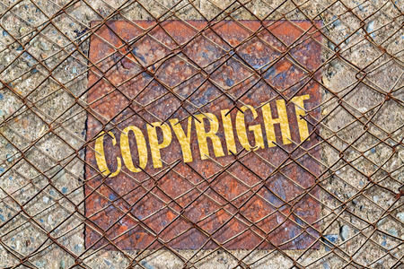 plagiarism: Word Copyright written in golden color under a broken wire fence