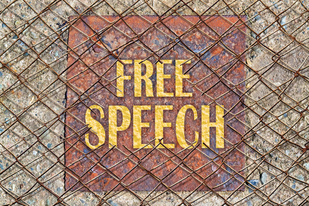 repress: Text Free Speech in golden color under a broken wire fence Stock Photo
