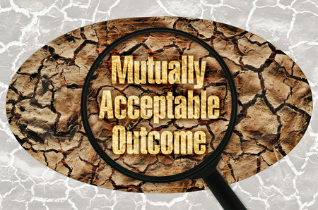 mutually: Text Mutually Acceptable Outcome under a magnifier on abstract background