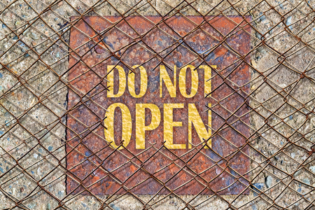 not open: Text Do Not Open in golden color under a broken wire fence