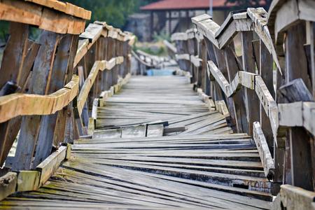 Close-up van een misvormd en vervallen houten brug over de rivier