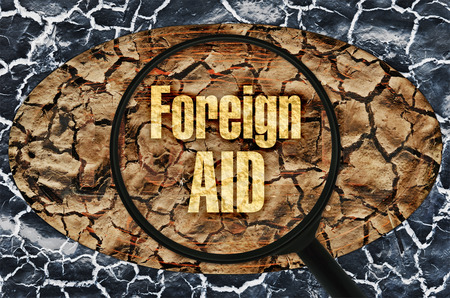 foundation problems: Text Foreign Aid under a magnifier on abstract background Stock Photo