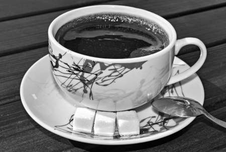 teaspoon: Cup of coffee with sugar cubes and teaspoon in black and white colors Stock Photo