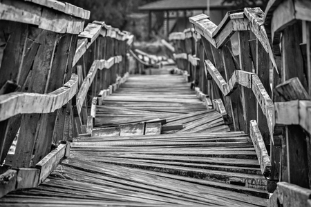 deformed: Closeup of a deformed and dilapidated wooden bridge in black and white Stock Photo