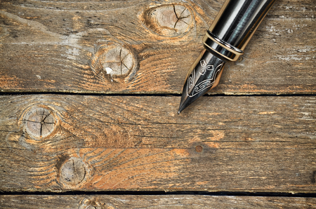 nib: Closeup of the feather of a fountain pen on wooden background