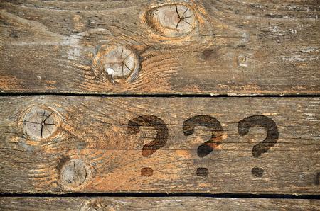 suspenso: Tres signos de interrogaci�n por escrito en el fondo de madera de �poca