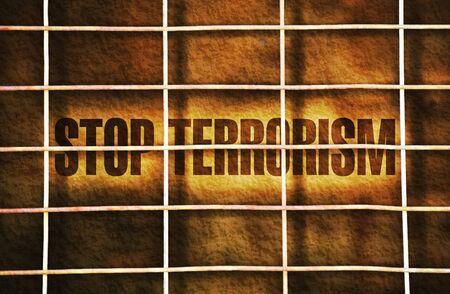 retaliation: Text Stop Terrorism written on dark background under a wire mesh Stock Photo