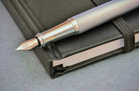 memo pad: Closeup of a silver fountain pen and closed memo pad on the table Stock Photo