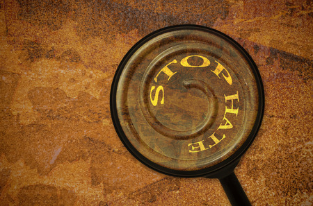hate: Text Stop Hate written on a spiral under a magnifier