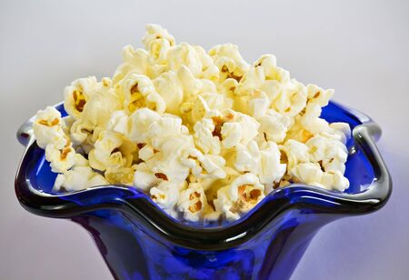 popcorn bowls: Closeup of homemade popcorn in blue glass on bright background Stock Photo